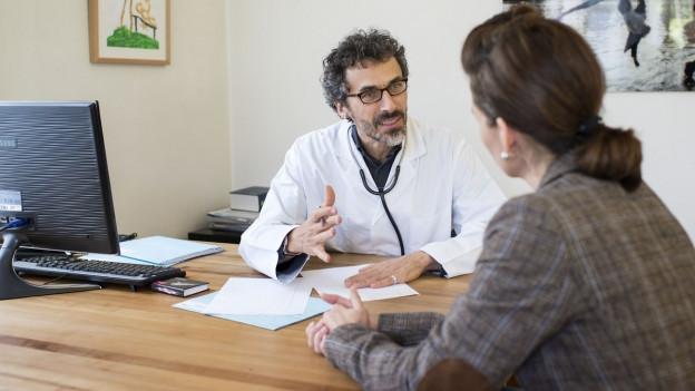 Ein Arzt sitzt mit einer Patientin an einem Tisch.