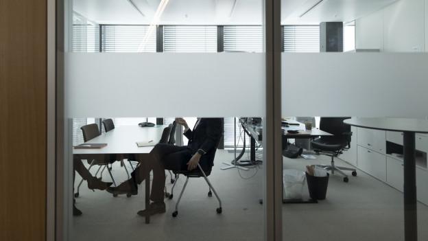 Ein Mann sitzt in einem Büro mit Glasscheiben.
