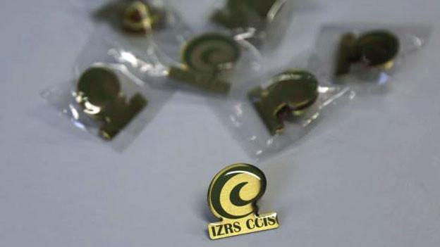 Pin mit dem Logo des Islamischen Zentralrates Schweiz.