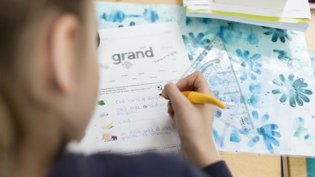 Eine Primarschülerin schreibt einen Französischtest.