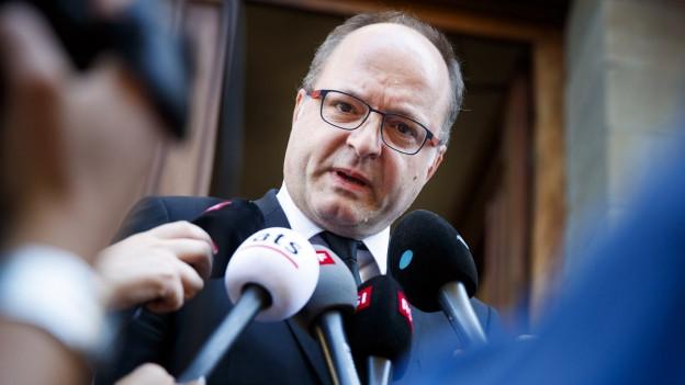 Einem Mann mit Brille werden eine grosse Anzahl Mikrofone vors Gesicht gehalten.