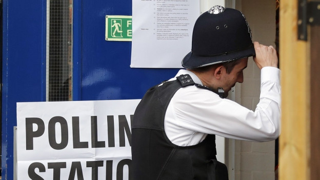 Ein Mann, von einem Schirm verdeckt, verlässt ein Wahllokal.