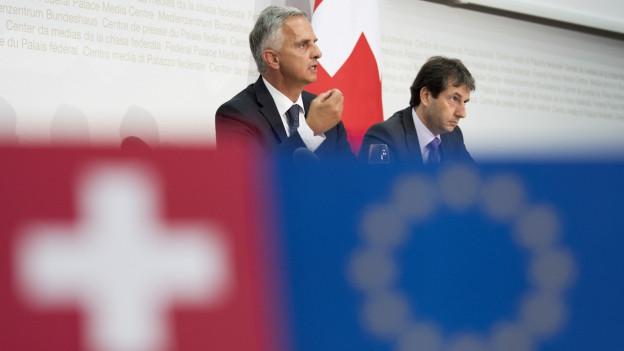 Aussenminister Burkhalter und Bundesratssprecher Simonazzi an der Medienkonferenz zu den EU-Verhandlungen, sie sitzen am Pult, davor die Schweizer und die EU-Flagge.