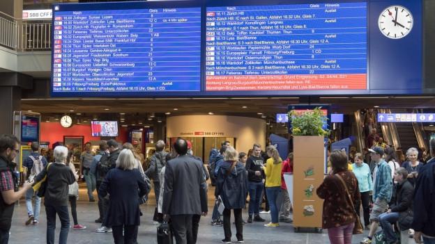 Reisende informieren sich im Hauptbahnhof Bern über die Abfahrten von Zügen.