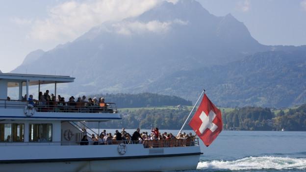 Ein Passagierschiff auf dem Vierwaldstättersee, der Bug mit der Schweizerfahne ist zu sehen, dahinter eine Bergkulisse.