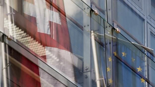 Die Fahnen der Schweiz und der EU spiegeln sich in einem Bürogebäude. Die stockende Zusammenarbeit hat nun Konsequenzen: Die Direktion für Zusammenarbeit und Entwicklung schliesst ihre Büros in fünf osteuropäischen Ländern.