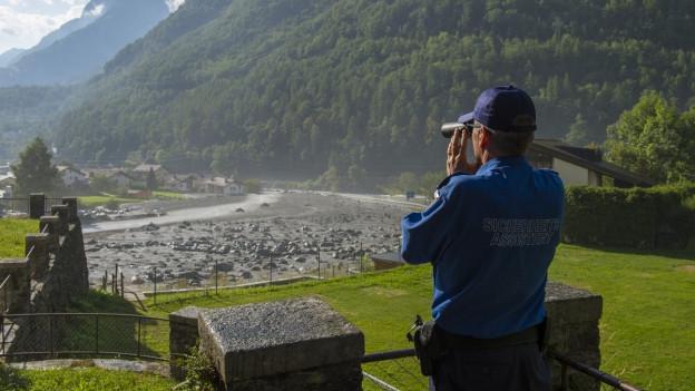 Ein Mann schaut mit Feldstecher auf die Felsbrocken bei Bondo, die im Hintergrund erkennbar ist.