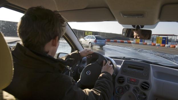 Auf dem Bild zu sehen ist ein Fahrschüler der ein Auto lenkt