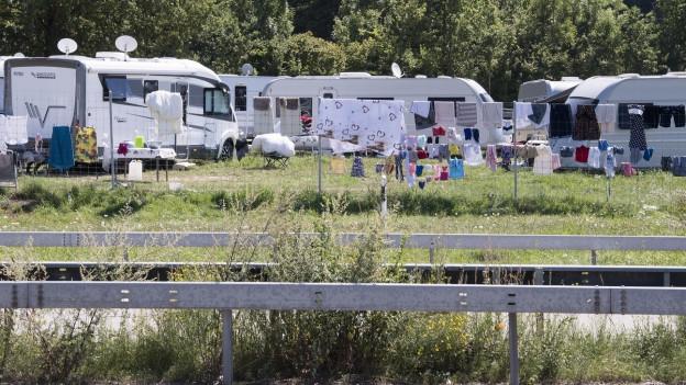 Auf dem Bild zu sehen sind Wohnwagen von Fahrenden und Kleider, die an einem Zaun trocknen