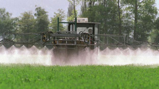 Ein Bauer in der Schweiz versprüht Pflanzenschutzmittel.