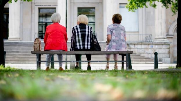 Renterinnen sitzen auf einer Bank im Park.