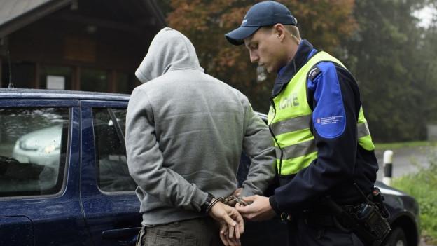 Ein Grenzwächter in gelber Weste führt einen Mann in Kapuzenpulli in Handschellen ab, sie stehen vor einem Auto.
