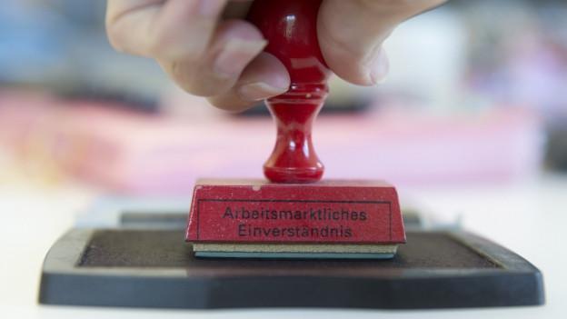 Eine Hand hält einen Stempel mit der Aufschrift «Arbeitsmarktliches Einverständnis».