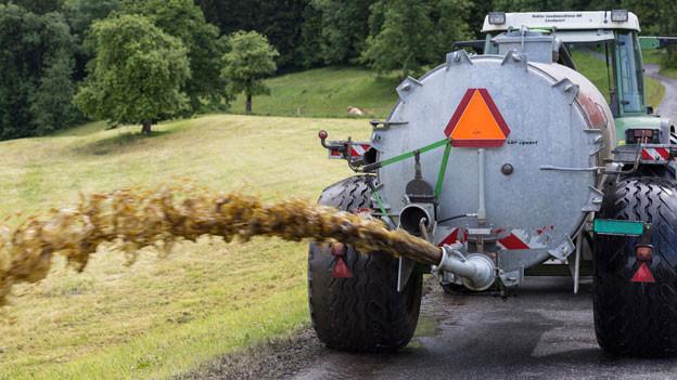 Bauer bespritzt sein Feld mit Gülle.