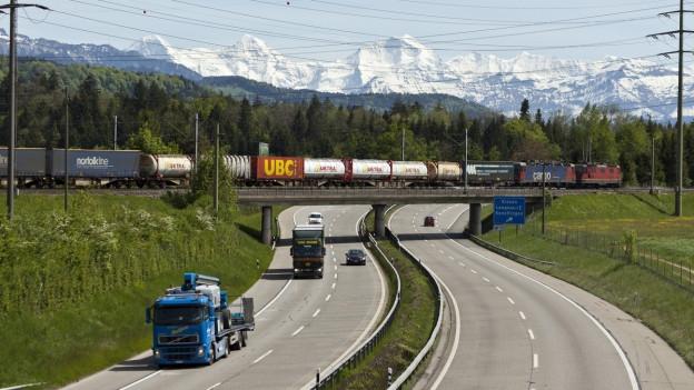LKW fahren auf der Autobahn, im Hintergrund sind Eiger, Moench und Jungfrau zu sehen.