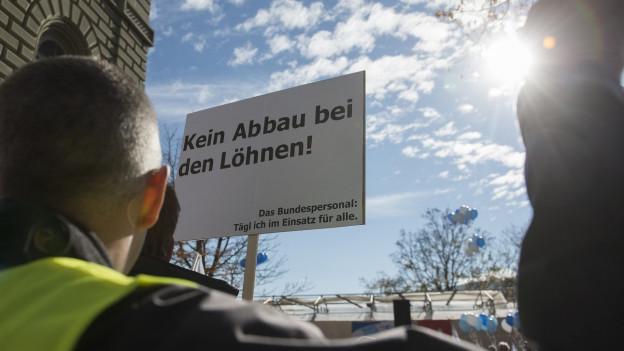 Beim Bundespersonal hat man keine Freude an den Sparplänen von FDP und SVP. Schon 2015 übergaben die Bundesangestellten eine Petition gegen den Abbau bei Löhnen und Arbeitsbedingungen. Das Bild zeigt einen Mann mit gelber Leuchtweste und ein Schild mit den Worten «Kein Abbau bei den Löhnen» vor dem Bundeshaus.
