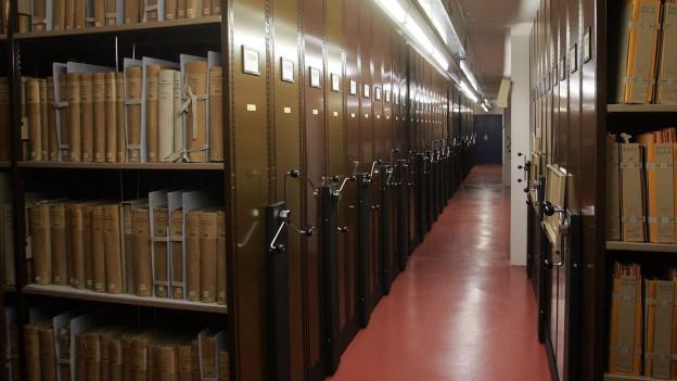 Innenraum im Bundesarchiv, zwischen zwei Gestellen voll mit Büchern in braunes Packpapier gewickelt.