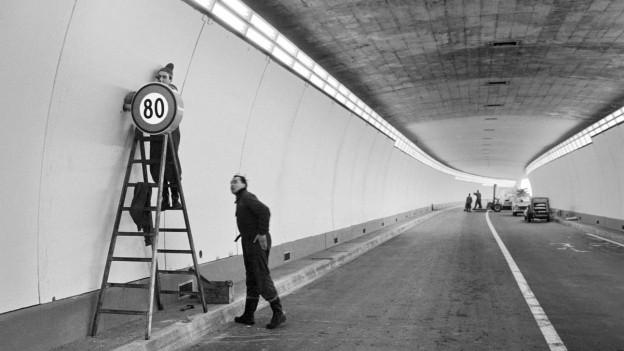 Auf dem Bild zu sehen sind zwei Männer die ein Geschwindigkeitsbegrenzungsschild im fertigen Tunnel anbringen