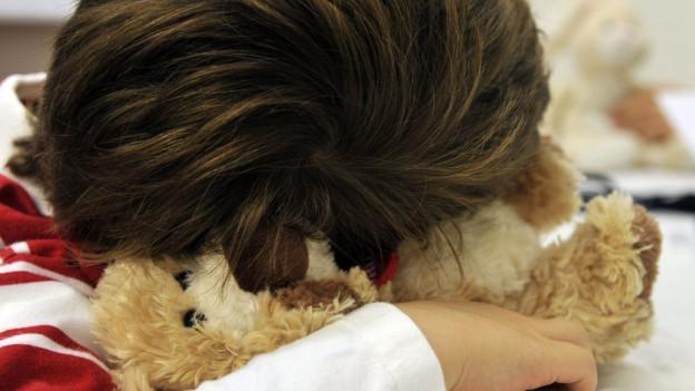 Ein Kind mit Teddy im Arm.