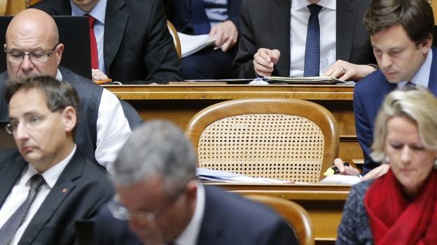 Parlamentarier sitzen im Nationalratssaal um einen leeren Sitz.