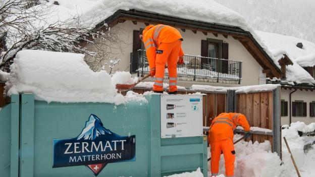 Gemeindemitarbeiter schippen Schnee in Zermatt.