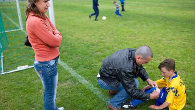 Ein Vater betreut seinen Sohn auf dem Fussballplatz.
