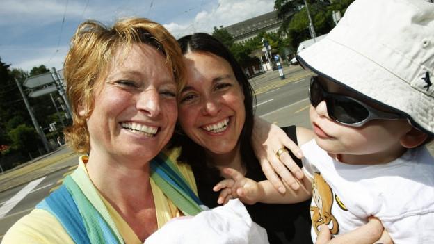 Ein lesbisches Paar lächelt in die Kamera, eine der Frauen hält ein Baby im Arm. Schon 2009 forderte das Komitee «Familienchancen» die Gleichstellung homosexueller Paare in Sachen Adoption.
