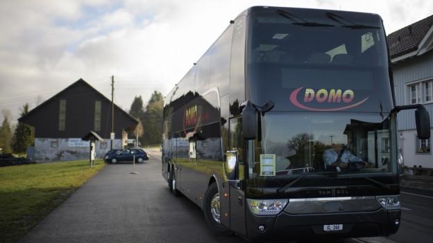 Ein Fernbus fährt durch einen Schweizer Ort.