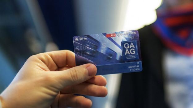 Eine Hand hält ein GA, dahinter sind man Schal und Uniform einer Kondukteurin im Zug.