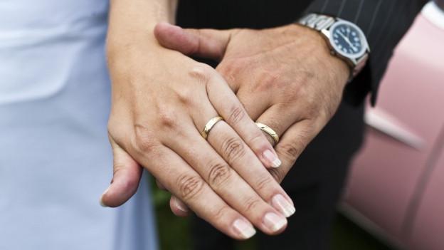 Eheringe an den Händen eines Ehepaars.