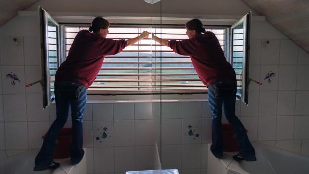 Eine Frau steht auf der Badewanne und reinigt das Badezimmerfenster, sie ist im Spiegel doppelt zu sehen.
