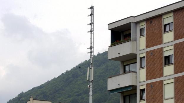Eine Mobilfunkantenne neben einem Mietshaus.
