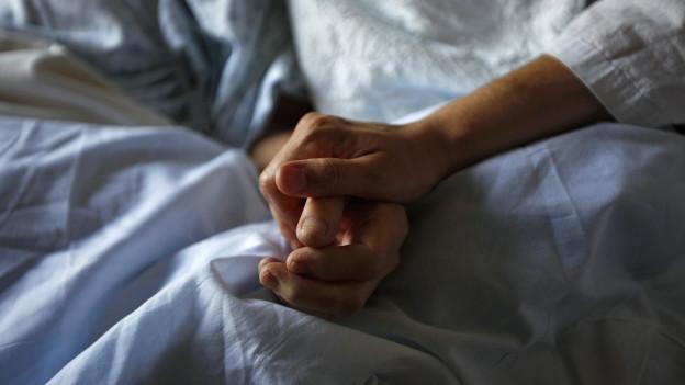 Eine Frau hält die Hand ihrer Mutter, die im Sterben liegt.