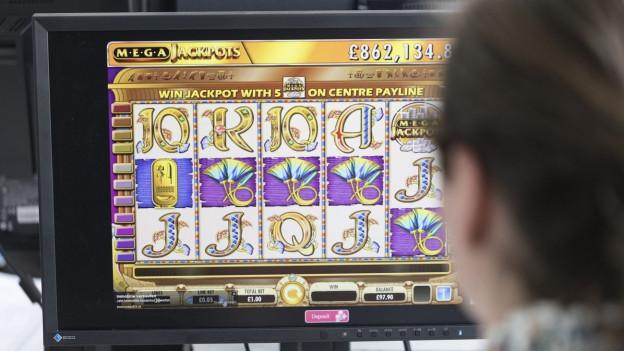 Eine Frau von hinten, sie schaut auf einen Computerbildschirm und spielt ein Online-Glücksspiel.