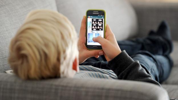 Ein junger Mann liegt auf einer Couch, und schaut in sein Smartphone.