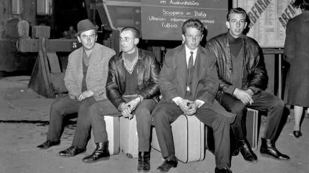 Vier Männer sitzen 1966 auf ihren Koffern am Bahnhof Zürich. Hinter ihnen überprüft eine Frau den Fahrplan.