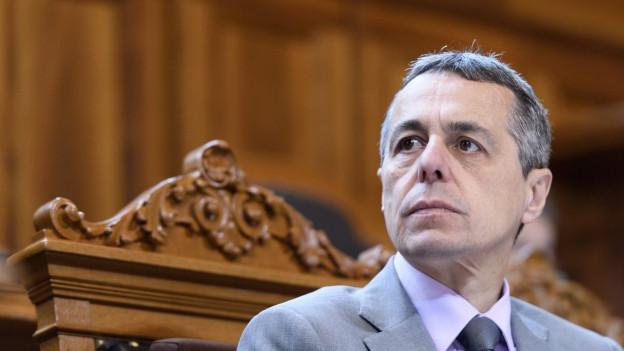 Aussenminister Ignazio Cassis im Ständeratssaal. Er blickt zur linken Seite. Im Hintergrund eine Holzwand.
