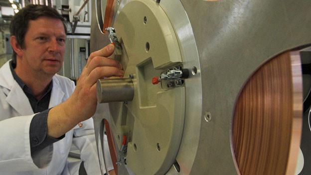Symbolbild. Ein Ingenieur befestigt eine Spule mit Kupferband in einer Produktionsanlage.
