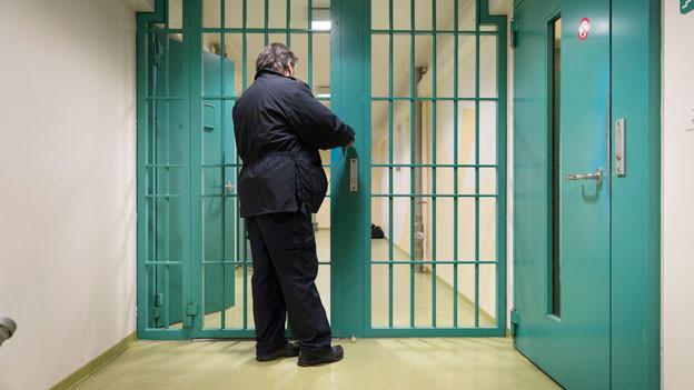 Ein Mitarbeiter schliesst eine Gittertür in einem Korridor im Flughafengefängnis.