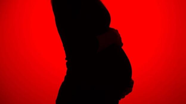Eine schwangere Frau wird in Silhouette gezeigt.