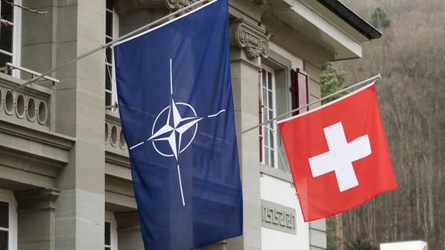Die Schweizer Fahne hängt neben einer Nato-Flagge.