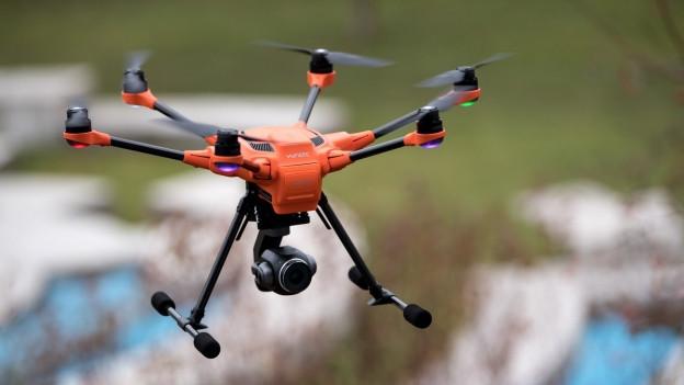 Eine Drohne schwebt über einer Stadt.