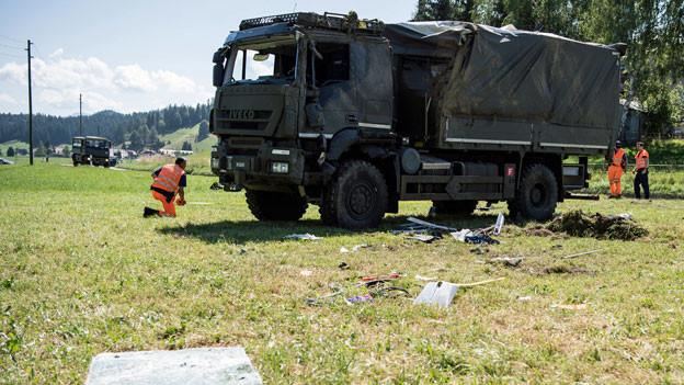 Zwei Polizisten untersuchen einen verunfallten Lastwagen der Armee, in Linden bei Oberdiessbach.