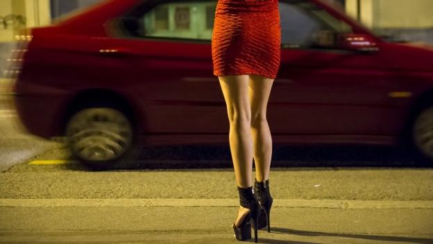 Eine Prostituierte geht auf ein herannahendes Auto zu.