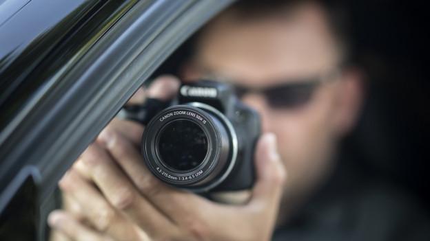 Ein Ermittler fotografiert aus einem Auto heraus.