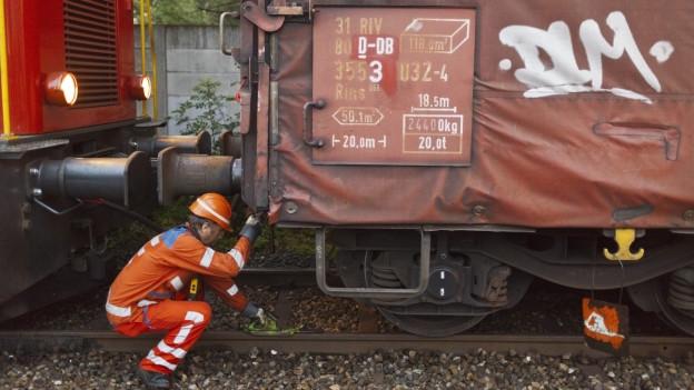 Ein Rangiermitarbeiter kniet zwischen zwei Güterwaggons.