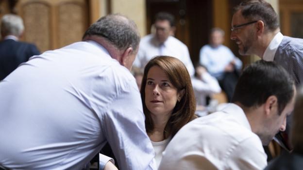 FDP-Präsidentin Petra Gössi im Nationalratssaal, umringt von Parteikollegen.