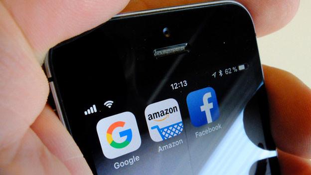 Die Logos der US-Internetkonzerne Google, Amazon und Facebook sind auf dem Display eines iPhone zu sehen.