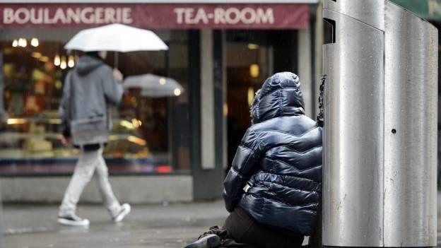 Ein Bettler sitzt in der Fussgängerzone von Lausanne am Boden neben einem Abfallkübel.