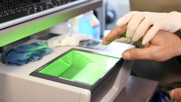 Ein Fingerscanner, er leutet grün, eine Hand im Gummihandschuh führt eine andere Hand ohne Handschuh über das Licht.,